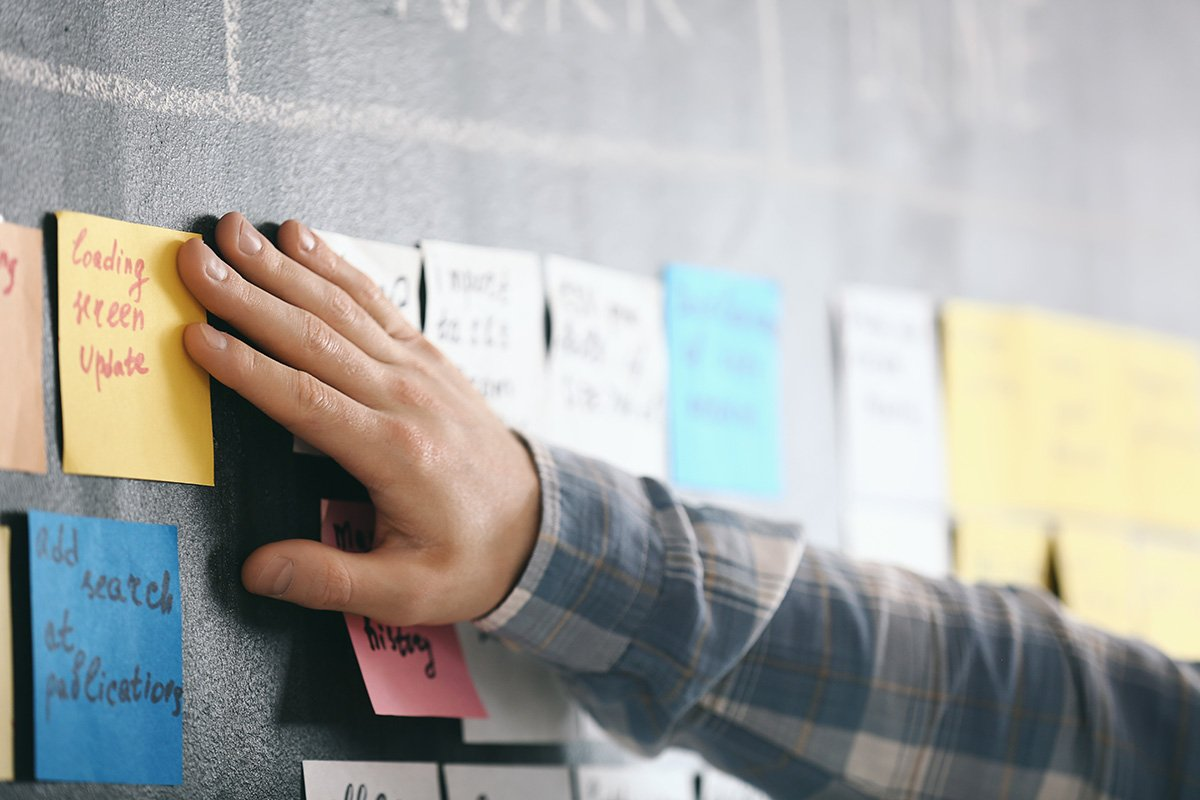 Hand with Post-its showing how some people visualize Scrum